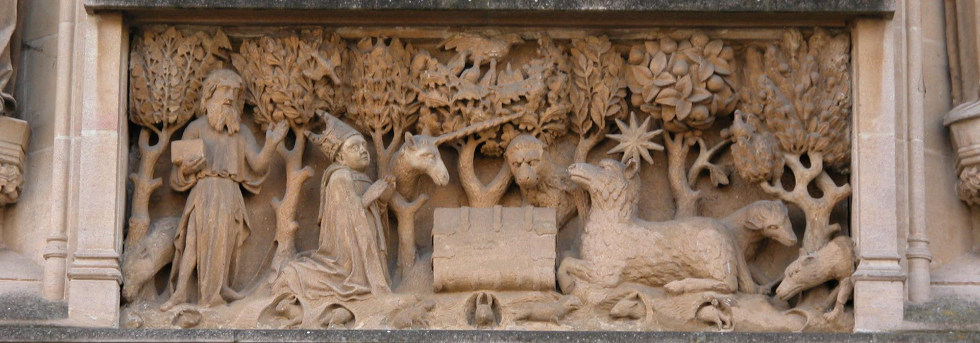 Central stone panel above the entrance to the College; it represents a book with the Agnus Dei on one side and St John the Baptist and the founder on the other side set in a l和scape background with various animals.