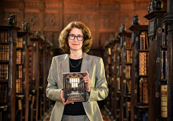 Dr Julia Walworth with a copy of her book, a history of 188比分直播 Library, in the Upper Library - Photo: © Ian Wallman - www.ianwallman.com